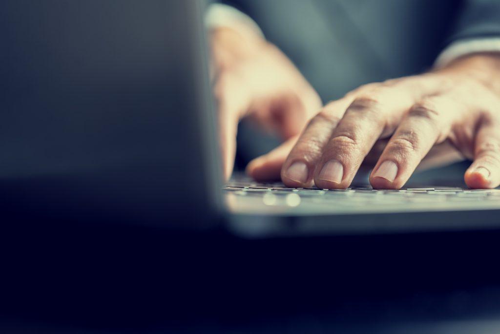 Manos escribiendo sobre un teclado de un portátil blog de aula
