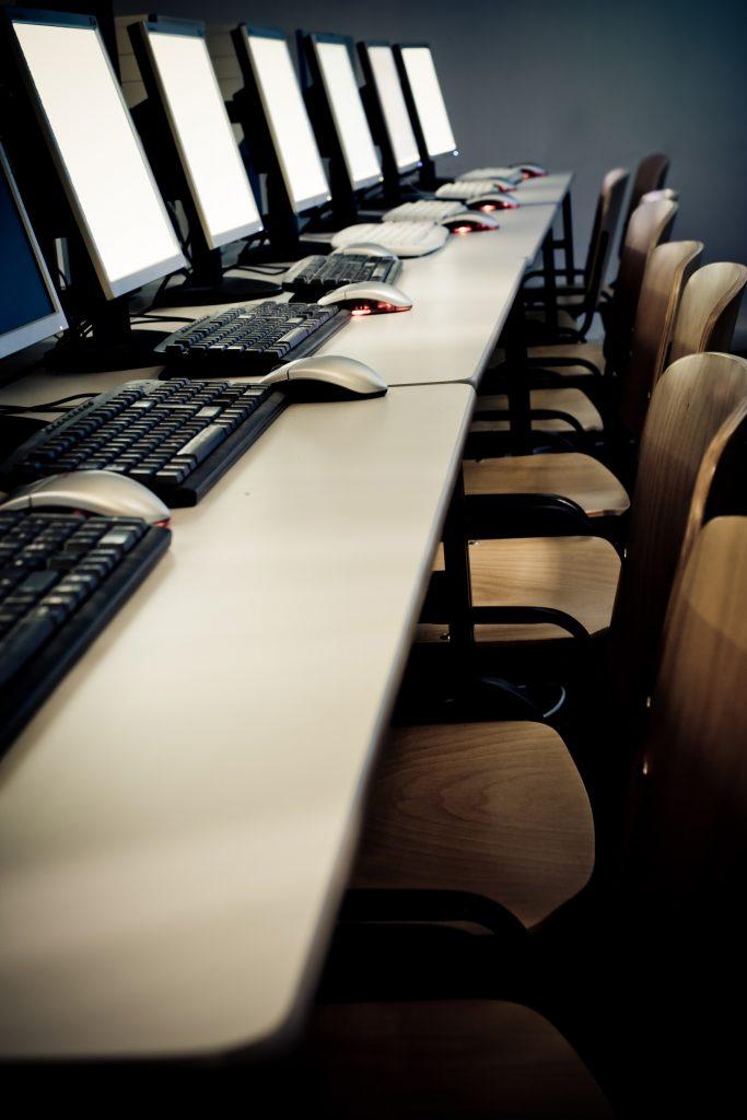 Una mesa repleta de puestos escolares, cada uno con un ordenador