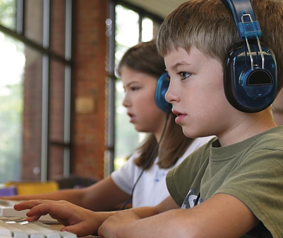 Niños con cascos y ordenador