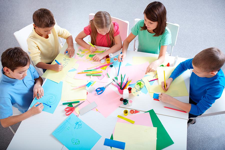 Niños alrededor de una mesa haciendo manualidades